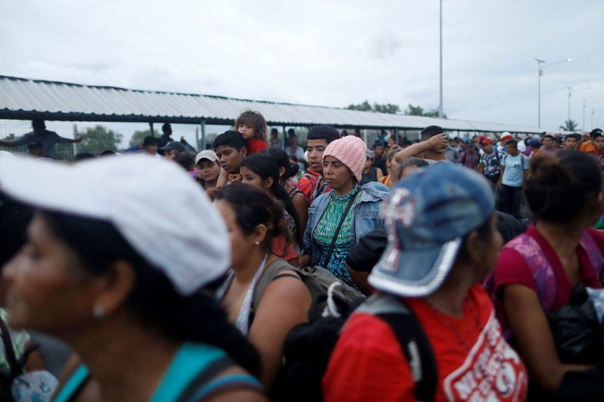 Honduran migrants, part of a caravan trying to reach the US, waiting on the bridge that connects Mexico and Guatemala as they try to avoid the border checkpoint in Ciudad Hidalgo, Mexico, on Oct 19, 2018.