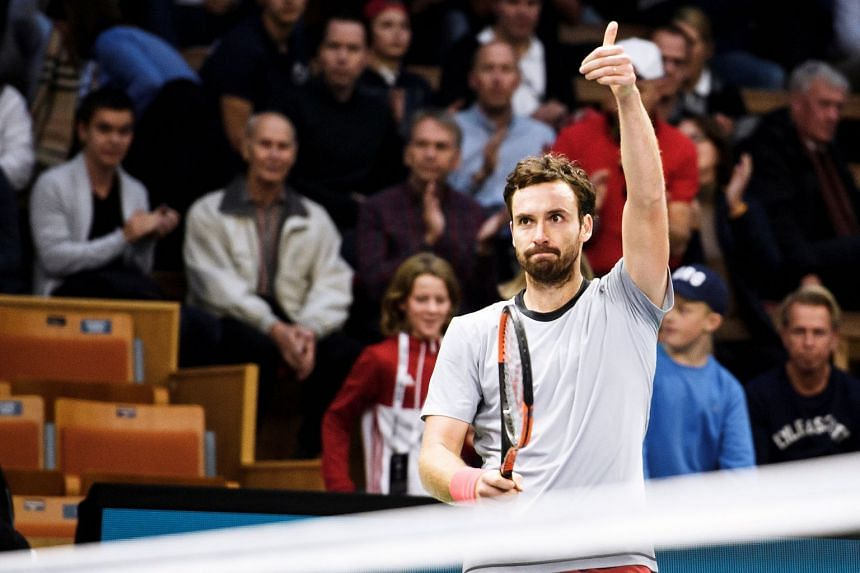 Gulbis reacts after winning with John Isner of the US.