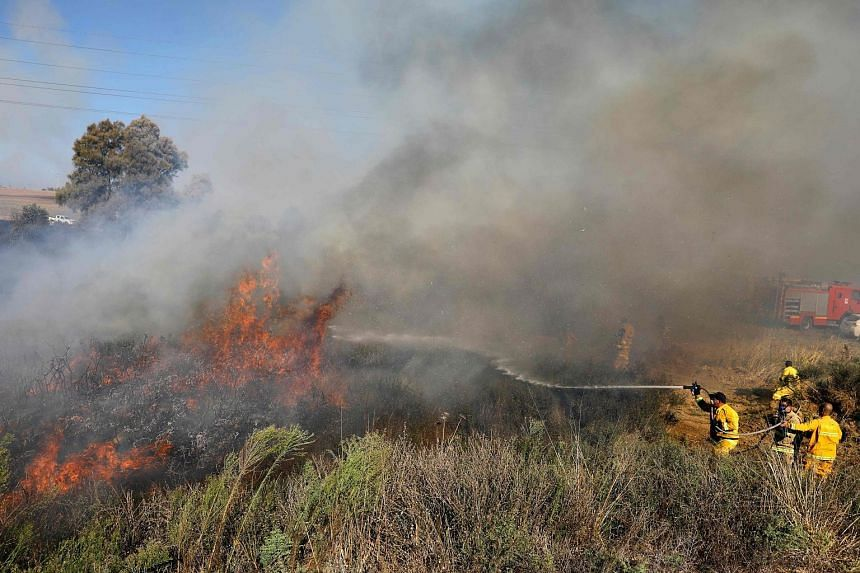 Israeli firefighters trying to extinguish a fire in a forest near the city of Sderot, along the border with the Gaza Strip, on July 31. The fire was caused by inflammable material attached to a balloon that was launched by Palestinian protesters from