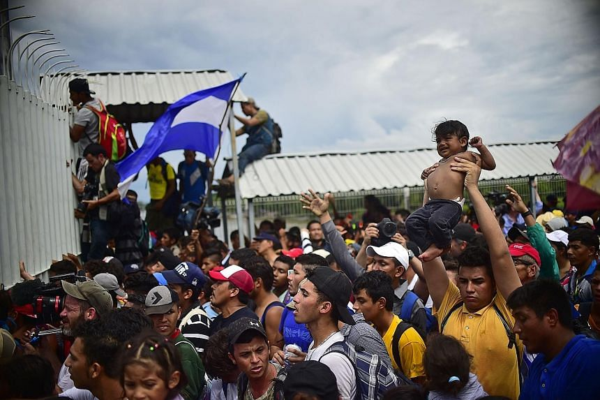 Above: Honduran migrants attempting to climb the gate at the Guatemala-Mexico border bridge last Friday. Left: Aerial view of the Honduran caravan, which has been stopped at a barrier on Mexico's southern border.