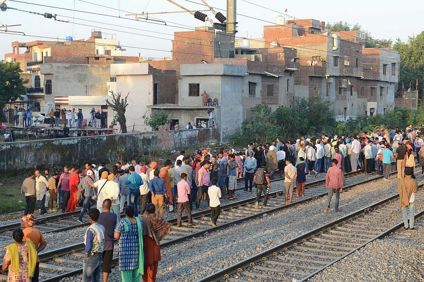 Grieving relatives and residents scouring the accident site yesterday, some looking for the belongings of their loved ones, after a train ran over revellers gathered on the railway tracks for a festival in Amritsar last Friday. Protesters called for