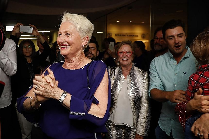 Independent candidate for Wentworth Kerryn Phelps (front) being congratulated by supporters as she arrives for a Wentworth by-election evening function at North Bondi Life Saving Club, Sydney, yesterday. With 54 per cent of the vote counted last nigh