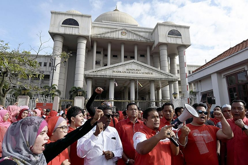 Supporters of Umno president Ahmad Zahid Hamidi outside the Kuala Lumpur Court Complex, where he was charged with criminal breach of trust, abuse of power and money-laundering last Friday.
