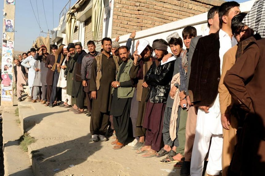 Afghan men stand in line to cast their votes outside a polling centre in Kabul, Afghanistan, on Oct 20, 2018.