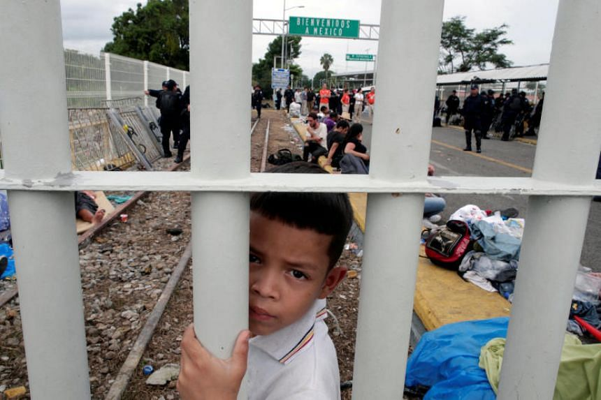 A Honduran migrant child looks though the gate on the bridge that connects Mexico and Guatemala in Tecun Uman, Guatemala, on Oct 20, 2018.