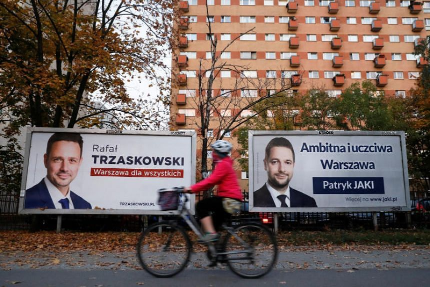 A woman rides a bicycle alongside campaign posters of Rafal Trzaskowski and Patryk Jaki, the two main candidates running for Warsaw mayor in a local election in Poland, in Warsaw, on Oct 18, 2018.