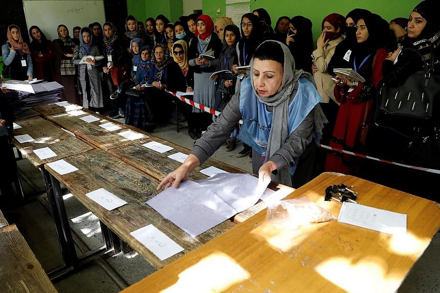 An election worker counting ballot papers at a polling station in Kabul yesterday. Initial Independent Election Commission figures showed that some three million voters turned up at 4,500 polling centres.