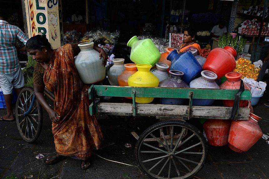 Women distributing water at a wholesale flower market during the Durga Puja festival in Chennai last week. Chennai, a coastal city in Tamil Nadu state, is situated on India's south-eastern coastline but it is not near any significant freshwater sourc