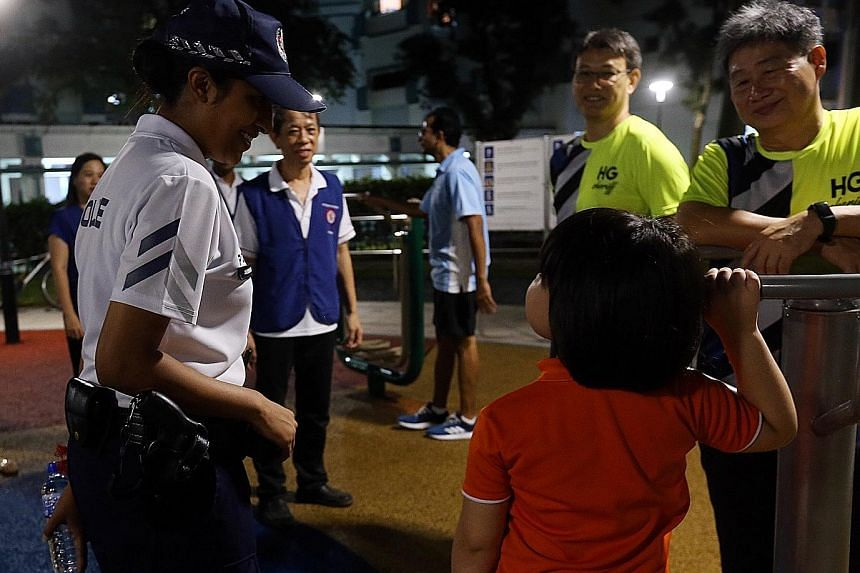 Staff Sgt Sri with a child at a playground while on patrol in Hougang. The 31-year-old is one of 26 CPU officers at Hougang Neighbourhood Police Centre.