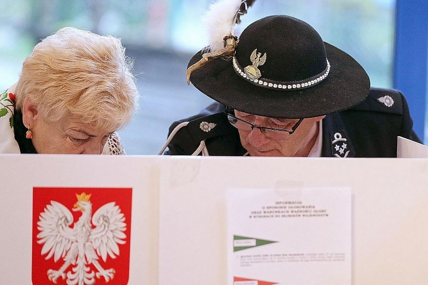 Gorals (highlanders) casting their votes in Zab, Poland, yesterday. Poles are electing councillors, district heads, and town and city mayors.