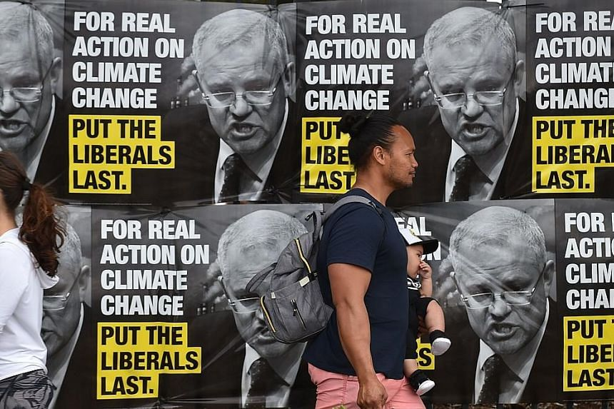 Election posters outside a polling station during the Wentworth by-election in Bondi Beach, Sydney, last Saturday. The Liberals remain deeply split on crucial issues such as climate change and immigration levels.