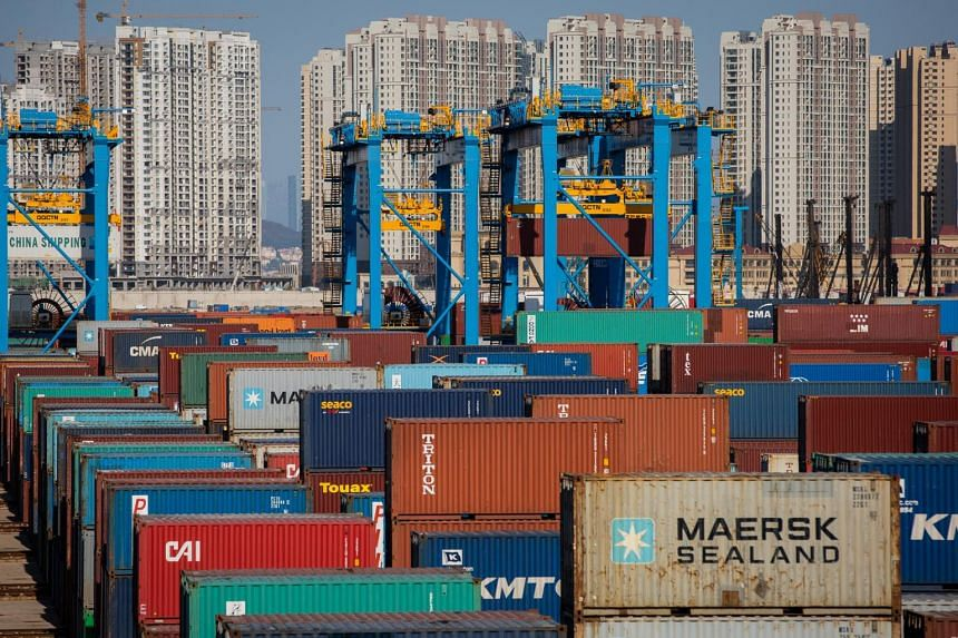 Containers are being transported by cranes at a fully automatic container berth of Port of Qingdao in eastern China's Shandong province.
