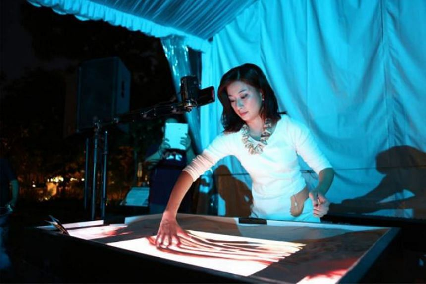 Artist Stacey Lee will be telling the story of Marina Barrage through a sand art performance at the carnival.