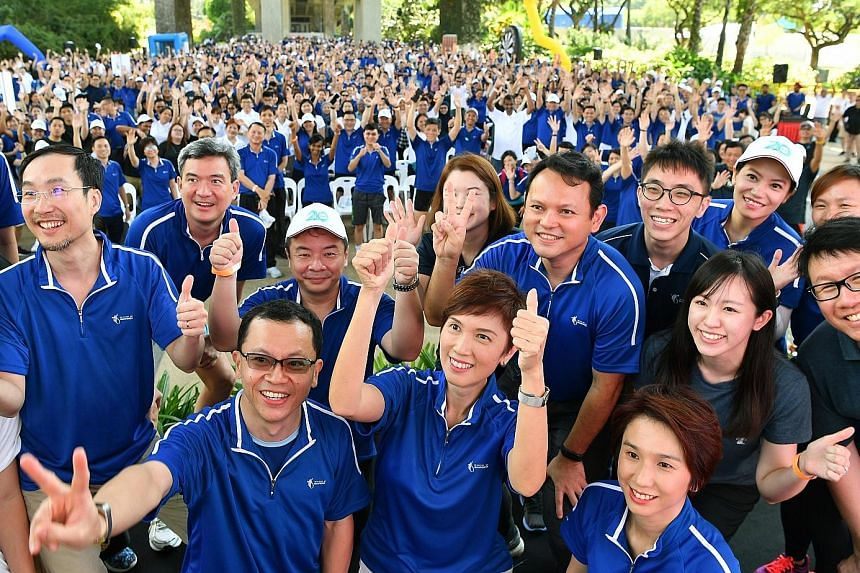 Manpower Minister Josephine Teo (centre) surrounded by (clockwise from left) her ministry's Permanent Secretary Aubeck Kam, Minister of State Zaqy Mohamad and Senior Parliamentary Secretary Low Yen Ling as they posed for a wefie with staff at the MOM