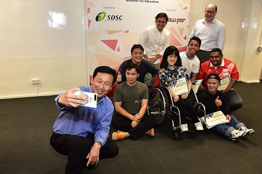 Education Minister Ong Ye Kung taking a wefie with (back row, from left) Singapore Disability Sports Council (SDSC) president Kevin Wong, Haw Par Corporation chief Wee Ee Lim and six para-athletes, who were among the recipients of the inaugural Haw P