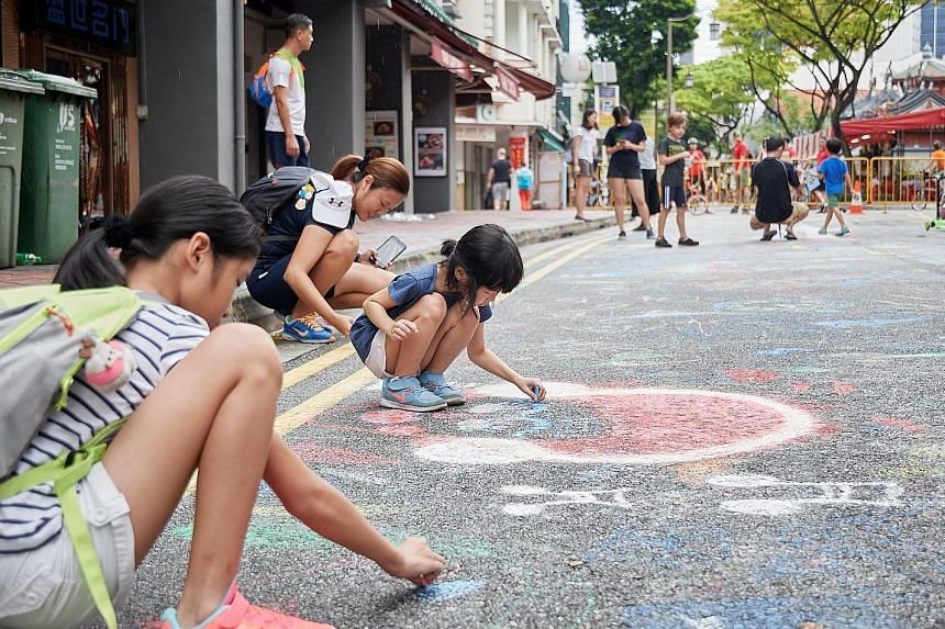 "People doodling on the road at the ""Walk the Chalk"" event in Telok Ayer Street during Car-Free Sunday SG in May. This weekend, visitors can try manoeuvring a pedal go-kart around Telok Ayer and the Central Business District."