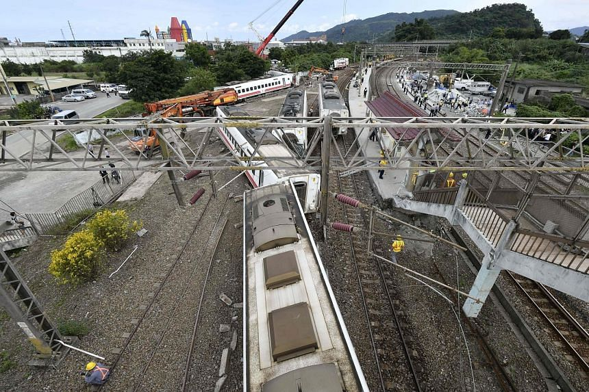 The scene of Sunday's rail disaster in Yilan, north-eastern Taiwan, which left 18 dead and 187 injured in the island's worst such incident in 27 years. All eight of the train's cars derailed, some knocking over concrete pylons.