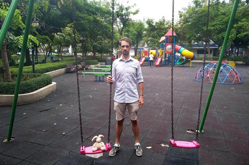 French Emmanuel de Fournas poses next to his child's doll at the playground of Benjasiri park in Bangkok, where he used to take his child to play.