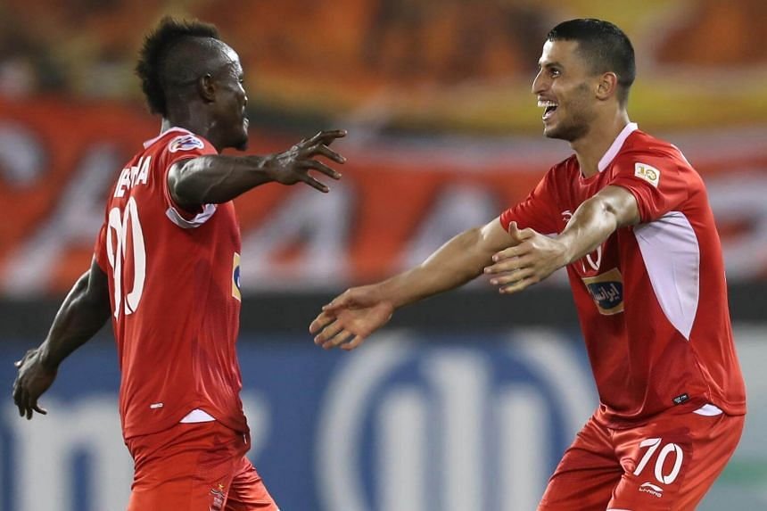 Persepolis FC's Ali Alipour celebrates with teammate Goodwin Mensha after scoring during the AFC Champions League semi-final first leg match between Al-Sadd SC FC and Persepolis FC at the Jassim Bin Hamad Stadium in Doha, on Oct 2, 2018.