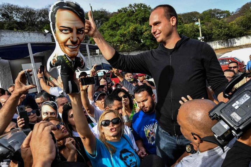 The son of Brazilian right-wing presidential candidate Jair Bolsonaro, Eduardo Bolsonaro, gives his thumb up to his father's supporters gathering in front of the Israelita Albert Einstein Hospital in Sao Paulo, Brazil, on Sept 16, 2018.