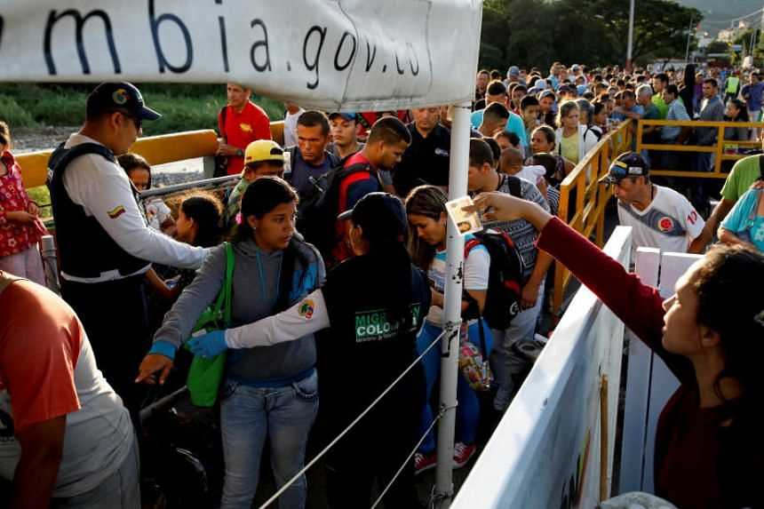 Colombian migration officers check the identity documents of people trying to enter Colombia from Venezuela, at the Simon Bolivar International bridge in Villa del Rosario, Colombia, on Aug 25, 2018.