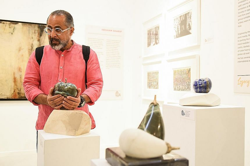 Writer and artist Ayman Jaafer (left) showing his artwork to visitors.