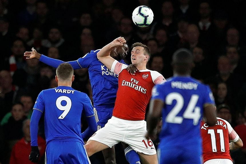 Arsenal's Rob Holding (in red) handling the ball after a tussle in the box with Leicester's Wilfred Ndidi during Monday's Premier League game at the Emirates. Leicester were 1-0 up at that time but referee Chris Kavanagh did not give a penalty and Ar