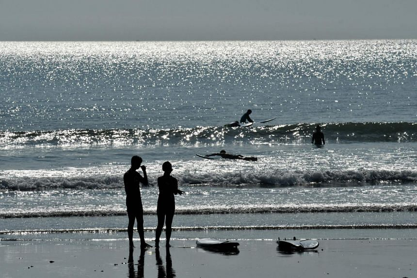Tourists enjoy a day out on Kuta beach, in Bali, on Oct 10, 2018