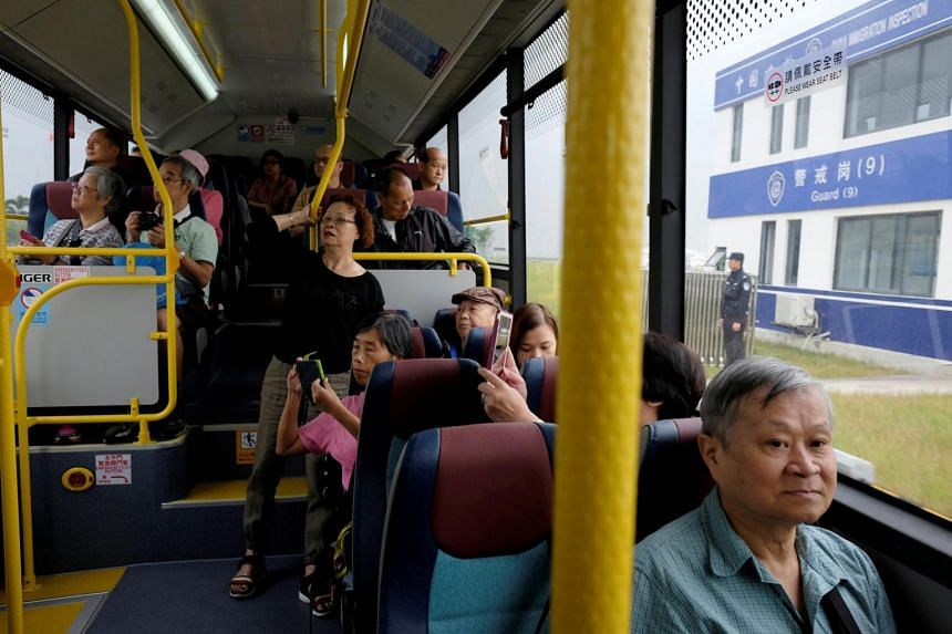Passengers look out as the bus passes a border checkpoint after crossing the Hong Kong-Zhuhai-Macau Bridge during its first day of operation, in Macau, on Oct 24, 2018.