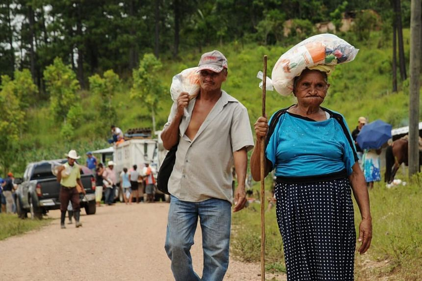 Honduran Tolupan natives and ladino people, receive food donations from the government at the Montana de la Flor, in Francisco Morazan department, Honduras, on Sept 1, 2018.