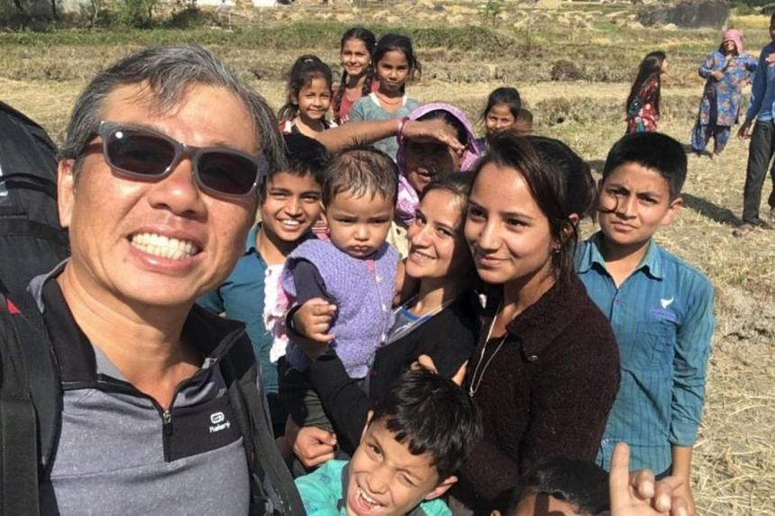 In a photo taken during his trip in Bir Billing, Mr Ng poses for a selfie with local children in Bir Billing after completing a flight.