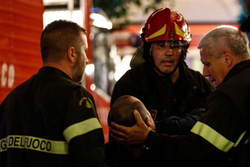 First responders tend to a wounded person on Piazza della Repubblica in central Rome.