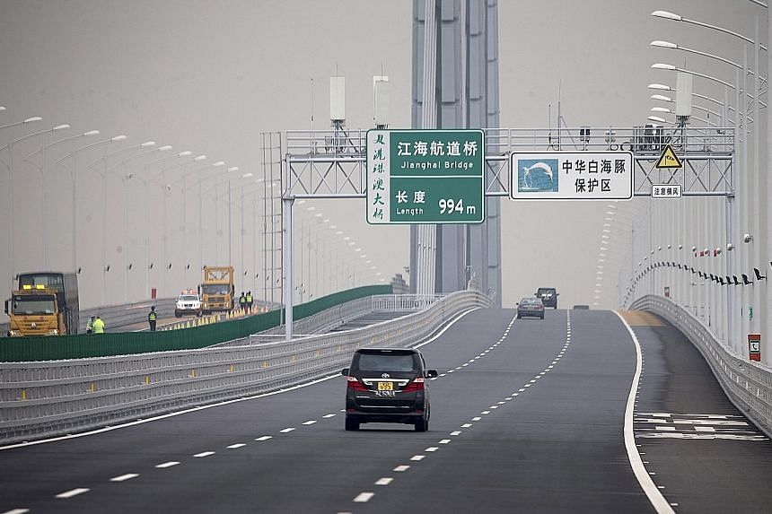 China-bound cars on the Hong Kong-Zhuhai-Macau bridge yesterday. The new 55km bridge took nine years to build and overran its budget after a two-year delay to its opening. Officials have said it will cut travelling time from Hong Kong International A