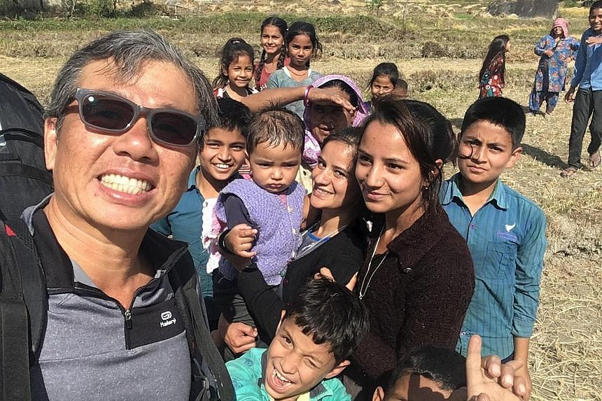 Mr Ng Kok Choong with local children in Bir Billing, India, last week after completing a flight. The day before he went missing, Mr Ng had cautioned other paragliders to be careful because of the treacherous weather conditions.