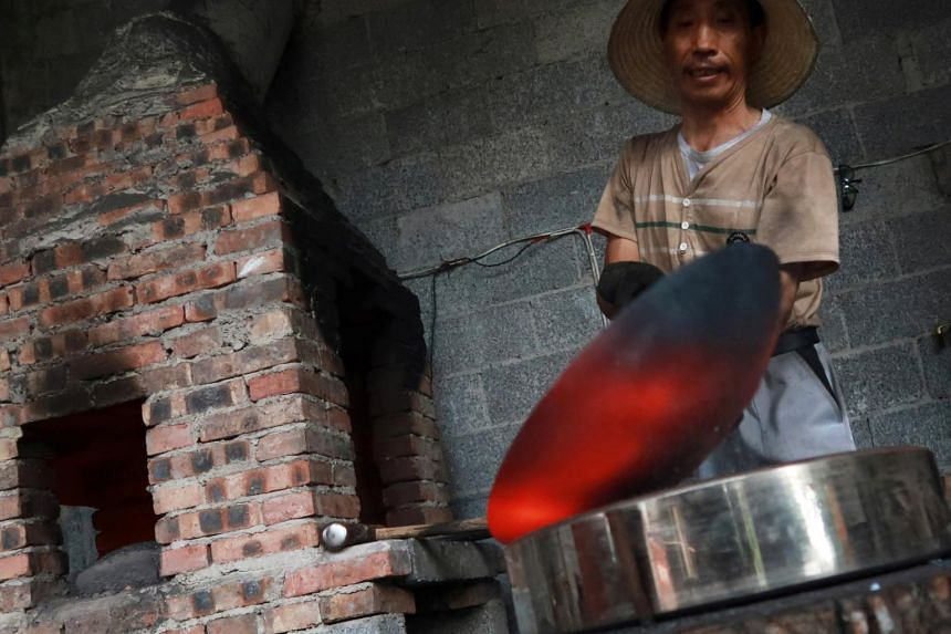A blacksmith works on a wok at a workshop for handmade woks in Datian village, China, on Aug 13, 2018.