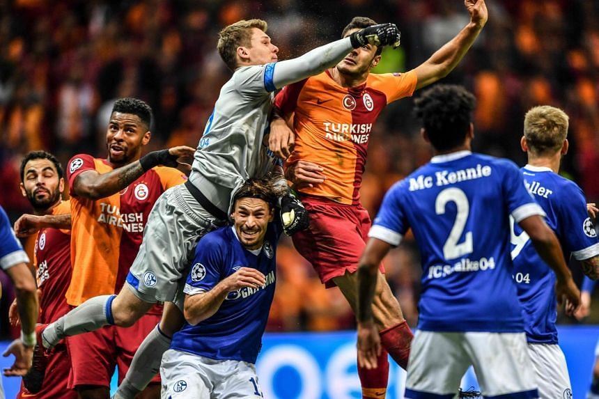 Schalke's German goalkeeper Alexander Nubel (centre) punches the ball clear of Galatasaray's players.