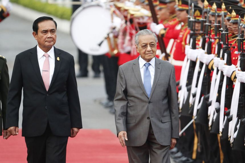 Malaysian Prime Minister Mahathir Mohamad, escorted by Thai Prime Minister Prayut Chan-o-cha, reviewing an honour guard during a welcoming ceremony yesterday at the government house in Bangkok.