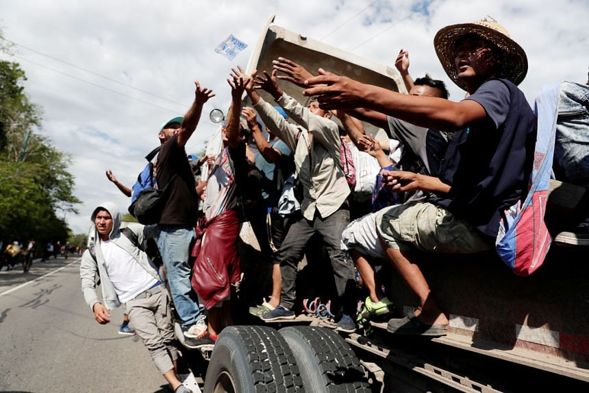 Hondurans fleeing poverty and violence in their country resting at a makeshift camp when their US-bound caravan stopped in Huixtla, Chiapas state, Mexico, on Tuesday. Central American migrants hitchhiking on a truck receiving water from a motorist in
