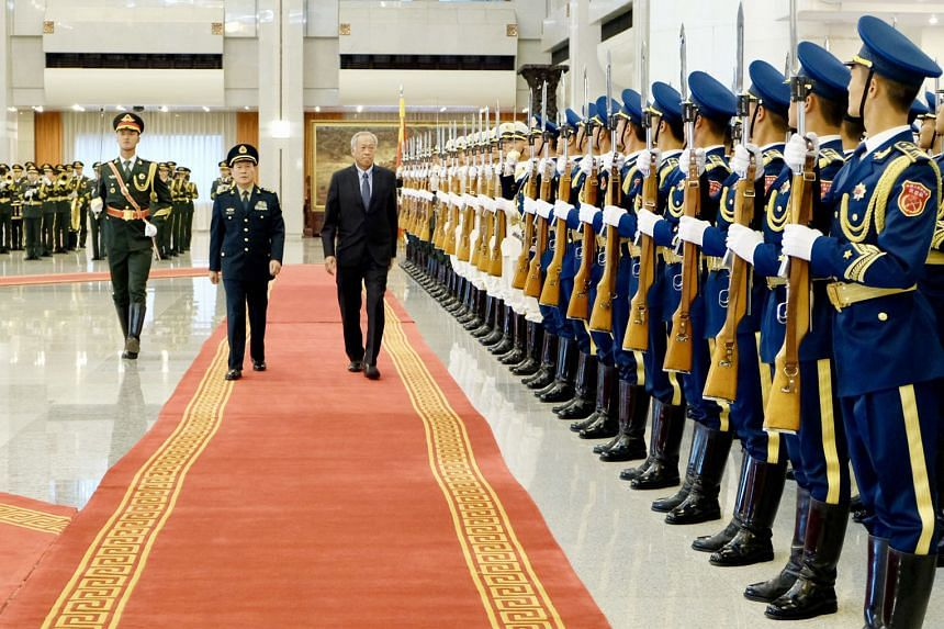 Minister for Defence Ng Eng Hen and Chinese Defence Minister Wei Fenghe reviewing a guard of honour in Beijing yesterday, where Dr Ng is on a five-day visit to China.