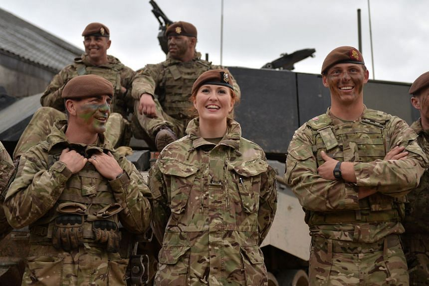 Newly-promoted Lance-Corporal Kat Dixon (centre) with other British Army service personnel in a photo released by the British Ministry of Defence.