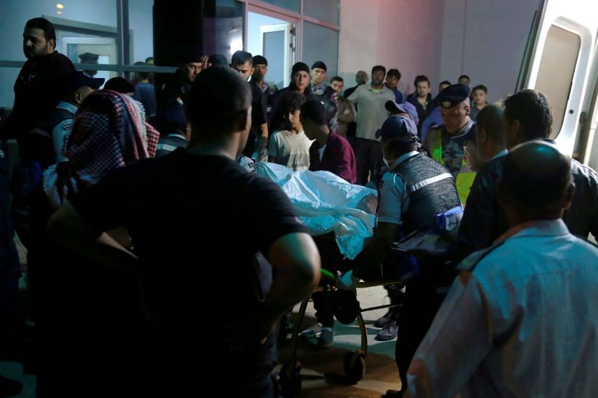 Residents and relatives of flood victims gather outside a hospital near the Dead Sea in Jordan.