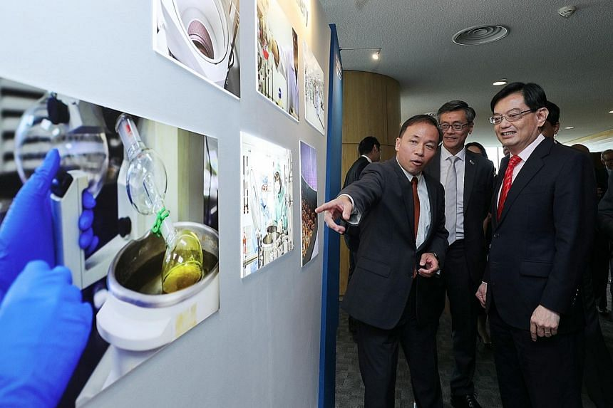 Professor Aaron Thean (left), co-director of the Applied Materials-NUS Advanced Materials Corporate Lab at NUS, showing Finance Minister Heng Swee Keat the exhibits displayed at the launch of the lab yesterday. With them was NUS president Tan Eng Chy