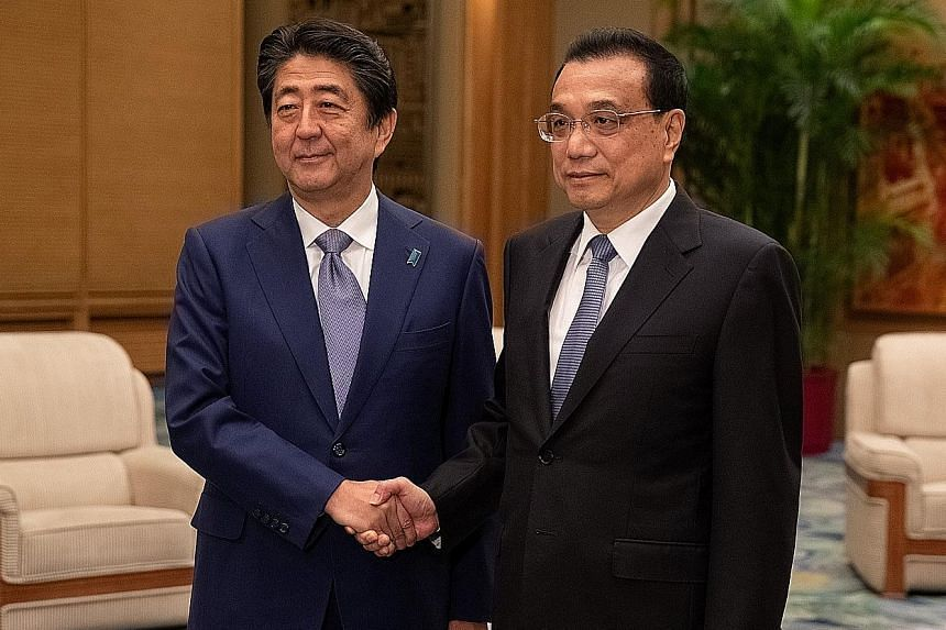 Japanese Prime Minister Shinzo Abe (left) meeting Chinese Premier Li Keqiang at the Great Hall of the People in Beijing yesterday. The two countries are seeking warmer ties amid trade friction with the US.
