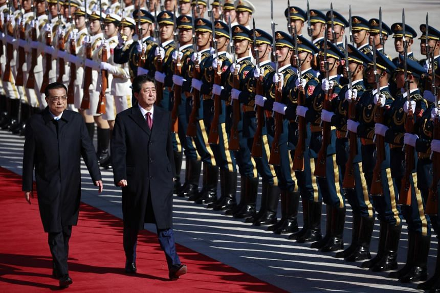 Japanese Prime Minister Shinzo Abe (left) and Chinese Premier Li Keqiang review an honour guard during a welcoming ceremony outside the Great Hall of the People in Beijing, on Oct 26, 2018.