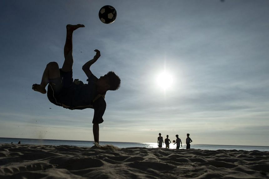 A boy plays football along a beach in the island of Boracay, Philippines, on Oct 25, 2018.