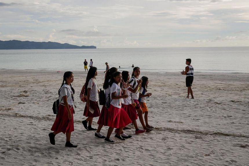 Students walk along the beach after school in the island of Boracay, Philippines, on Oct 17, 2018.