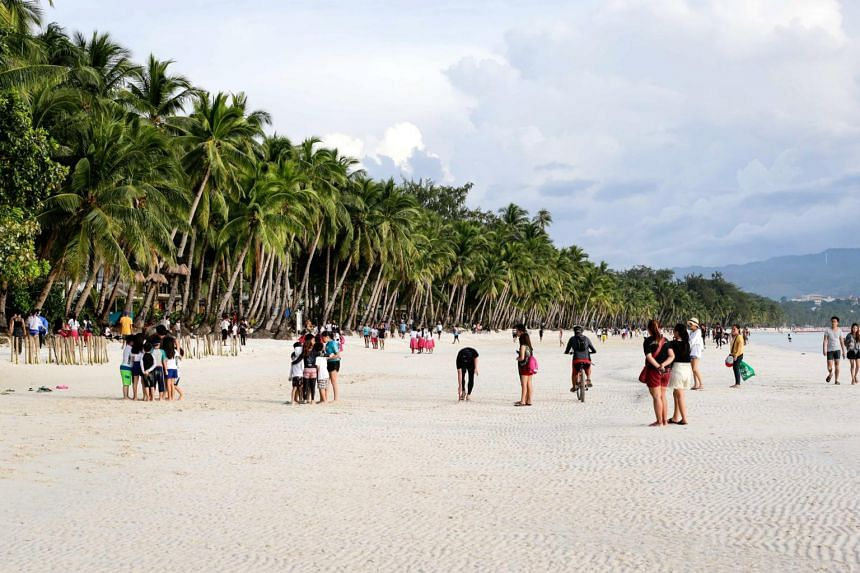 People frolic at the beach in the island of Boracay, Philippines, on Oct 16, 2018.