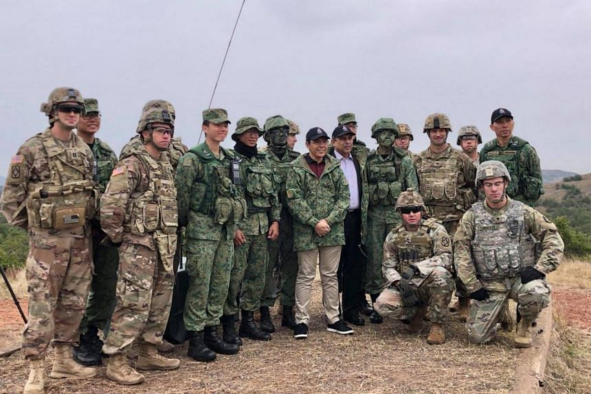 Senior Minister of State for Defence and Foreign Affairs Mohamad Maliki Osman (in blue cap and camouflage jacket) posing with troops participating in Exercise Daring Warrior at Fort Sill, Oklahoma, on Oct 24, 2018.