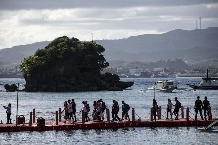 Tourists arrive at the Philippine island of Boracay on Oct 26, 2018. The Philippines re-opens its crown jewel resort island Boracay to holidaymakers on Oct 26, after a six-month clean up aimed at repairing the damage inflicted by years of unrestraine