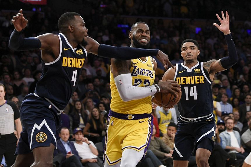 Los Angeles Lakers forward LeBron James (centre) attempts to drive the ball past Denver Nuggets forward Paul Millsap (left) during the second half at the Staples Center, on Oct 26, 2018.